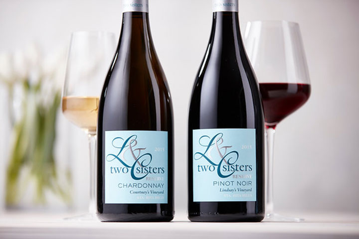 Two Sisters Pinot Noir and Chardonnay bottles next to wine glass