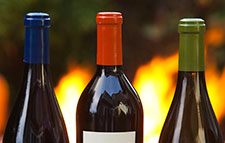 Close up of three wine bottles with fire in the background