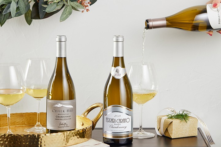 Two white wine bottles on holiday table with wine being poured